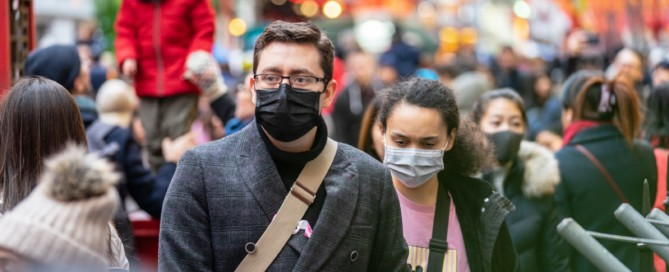 Crowd of people walking down the street with masks on